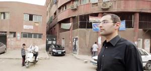 أيمن سباعي أمام المدخل الرئيسي لمستشفى بولاق العام (من وثائقي: امتلك المعلومة).