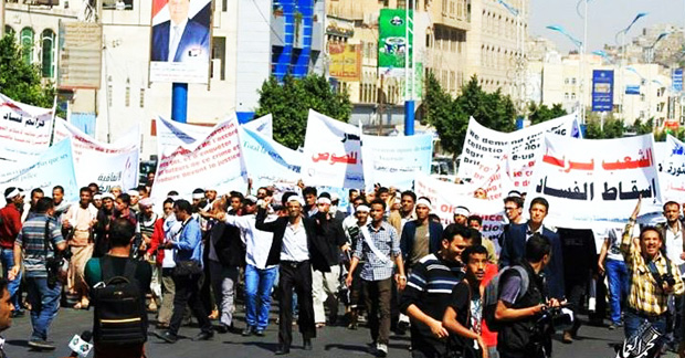 """Protestors holding signs saying """"The people want the downfall of corruption""""."""