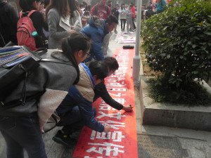 Chinese students sign a petition against corruption
